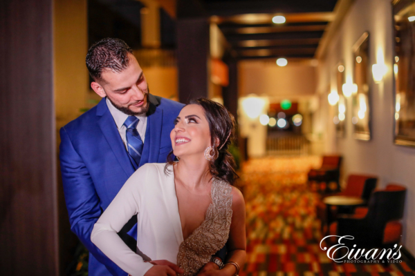 couple in a hotel lobby posing for a engagement photographer