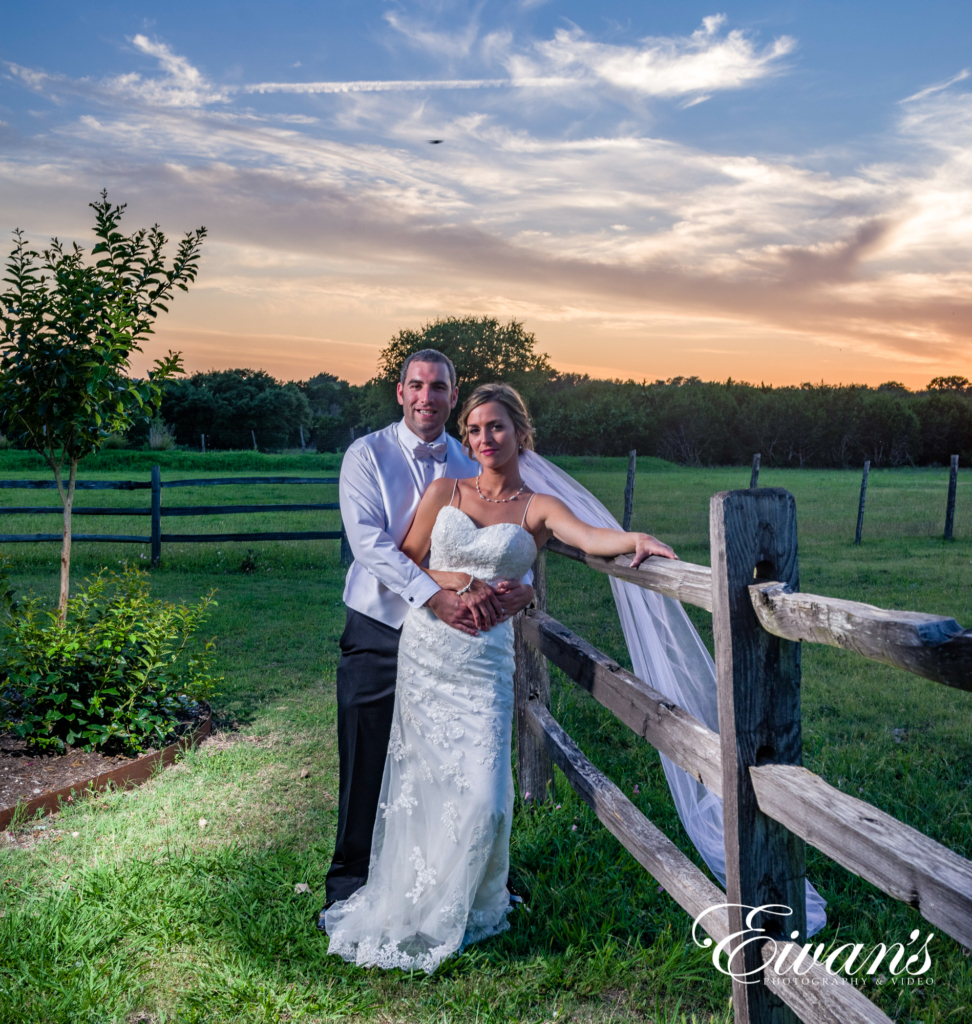 married couple posed on the barn fence in the sun set