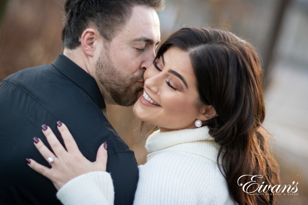 engaged man kissing his fiancee on the cheek